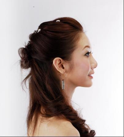 如图片中的女主角将头发一层层往后梳,然后在脑后盘出花朵形状的圆髻图片